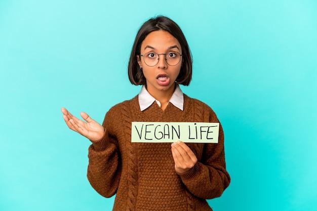 Молодая латиноамериканская женщина смешанной расы, держащая плакат веганской жизни, удивлена и шокирована.