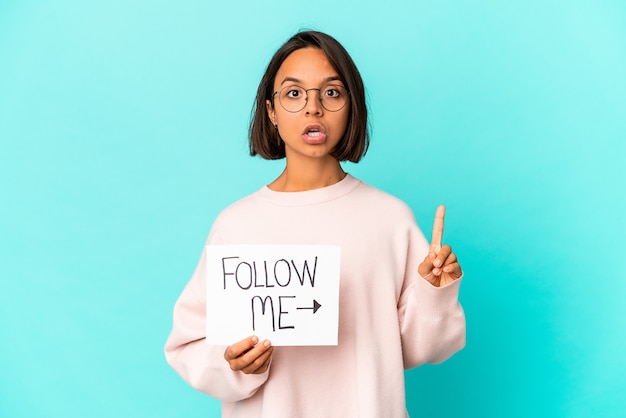 Young hispanic mixed race woman holding a follow me placard having some great idea, concept of creativity.