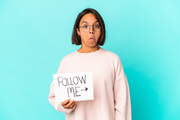 Young hispanic mixed race woman holding a follow me placard shrugs shoulders and open eyes confused