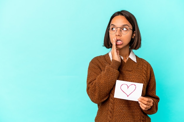 Young hispanic mixed race woman holding a heart paper is saying a secret hot braking news and looking aside