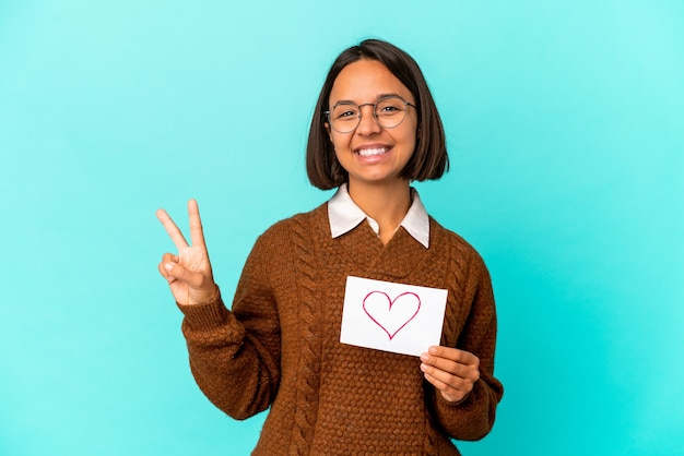 Young hispanic mixed race woman holding a heart paper showing number two with fingers.