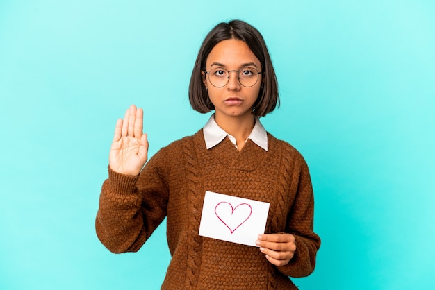 Young hispanic mixed race woman holding a heart paper standing with outstretched hand showing stop sign, preventing you.