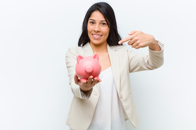 Young hispanic pretty woman with a piggy bank