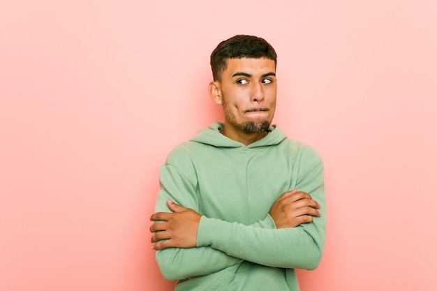 Young hispanic sport man confused, feels doubtful and unsure.