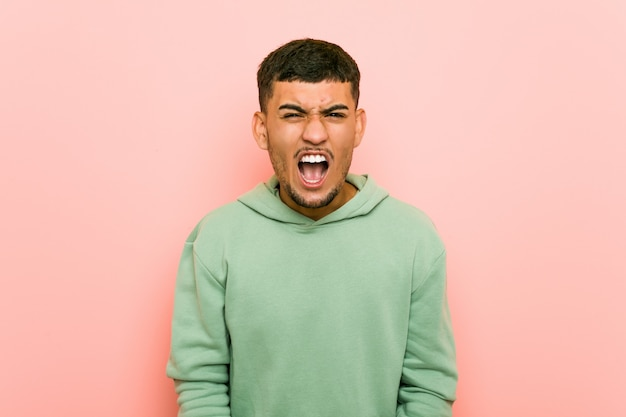 Young hispanic sport man screaming very angry and aggressive.
