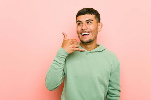 Young hispanic sport man showing a mobile phone call gesture with fingers.