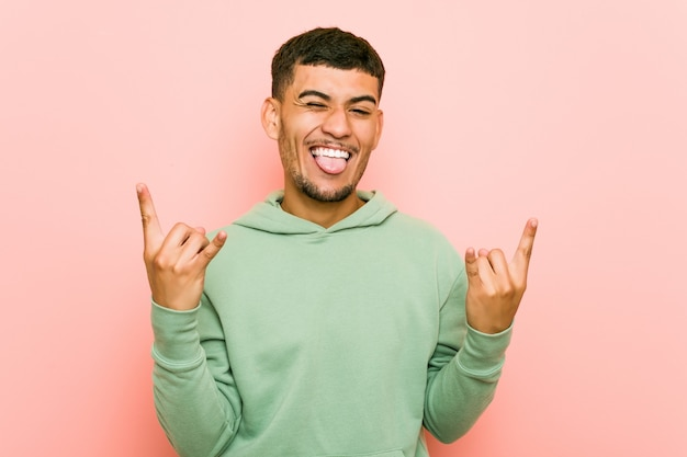 Young hispanic sport man showing rock gesture with fingers