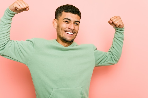 Young hispanic sport man showing strength gesture with arms, symbol of feminine power