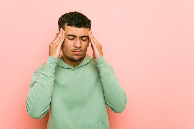 Young hispanic sport man touching temples and having headache.