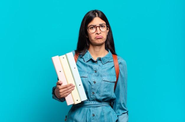 不幸な表情で悲しみと泣き言を感じ、否定的で欲求不満の態度で泣いている若いヒスパニック系学生女性