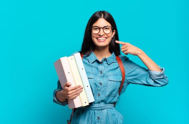 Молодая латиноамериканская студентка улыбается, уверенно указывая на собственную широкую улыбку, позитивное, расслабленное, удовлетворенное отношение