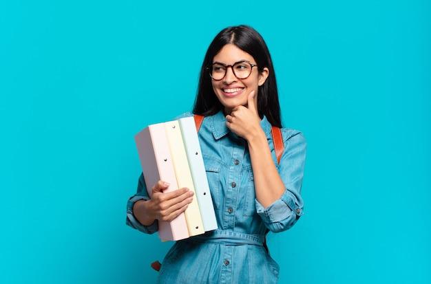 Молодая латиноамериканская студентка улыбается со счастливым, уверенным выражением лица, положив руку на подбородок, задается вопросом и смотрит в сторону