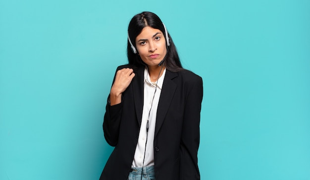 Young hispanic telemarketer woman looking arrogant, successful, positive and proud, pointing to self
