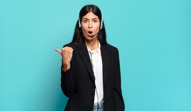 不信に驚いたように見える若いヒスパニックテレマーケティングの女性は、側面のオブジェクトを指して、すごい、信じられないほど言っています