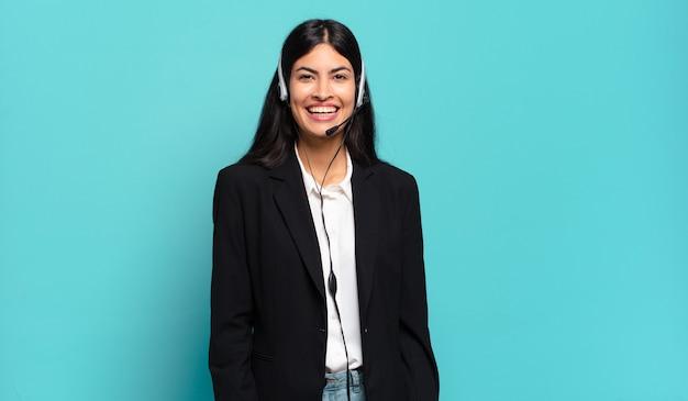 Молодая латиноамериканская женщина-телемаркетинг выглядит счастливой и приятно удивленной, взволнованной, с очарованным и шокированным выражением лица