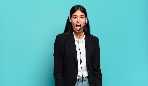非常にショックを受けたり驚いたりしている若いヒスパニックテレマーケティングの女性
