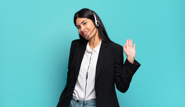 Молодая латиноамериканская женщина-телемаркетер счастливо и весело улыбается, машет рукой, приветствует и приветствует вас или прощается