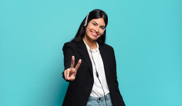 Young hispanic telemarketer woman smiling and looking happy, carefree and positive, gesturing victory or peace with one hand