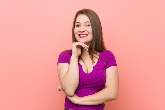 ピンクの壁に幸せで自信を持って笑って、手で顎に触れて、若いヒスパニック系の女性。