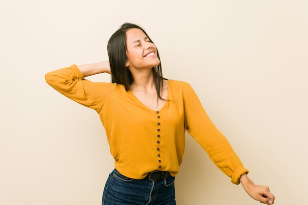 Young hispanic woman against a beige wall dancing and having fun.