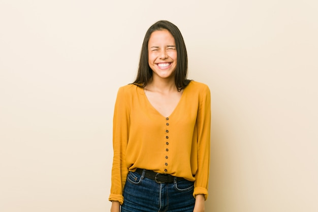 Young hispanic woman against a beige wall  laughs and closes eyes, feels relaxed and happy.