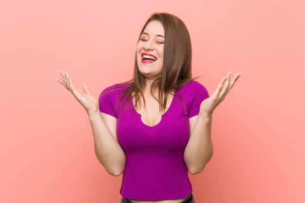 Young hispanic woman against a pink wall joyful laughing a lot. happiness .