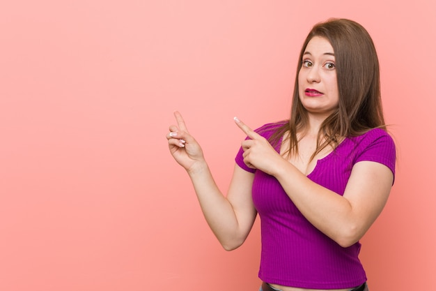 Young hispanic woman against a pink wall shocked pointing with index fingers to a copy space.
