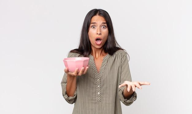 젊은 히스패닉계 여성은 믿을 수 없는 놀라움으로 놀라고, 충격을 받고, 놀라며 빈 그릇이나 냄비를 들고 있다