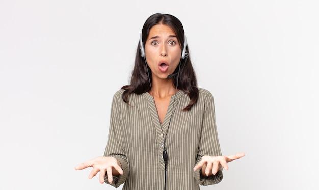 젊은 히스패닉계 여성은 헤드셋으로 믿을 수 없는 놀라움에 놀랐고 충격을 받았습니다. 텔레마케팅 개념
