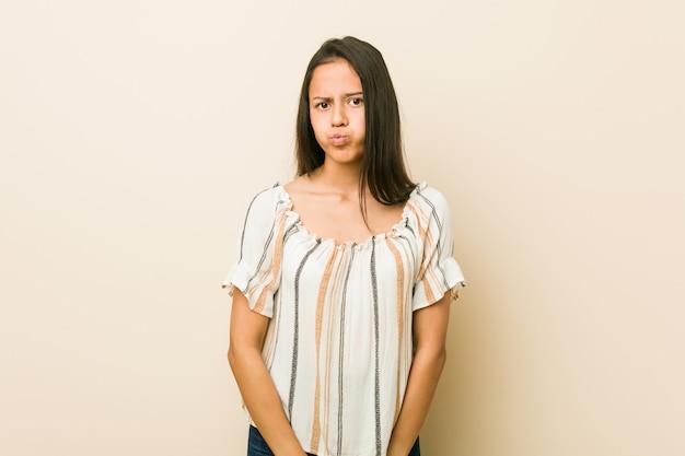 若いヒスパニック系女性は頬を吹く、疲れた表情をしています。表情のコンセプト。