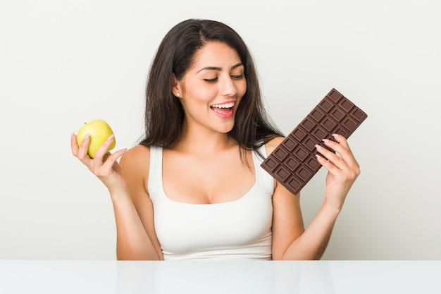 Young hispanic woman choosing between apple or chocolate tablet
