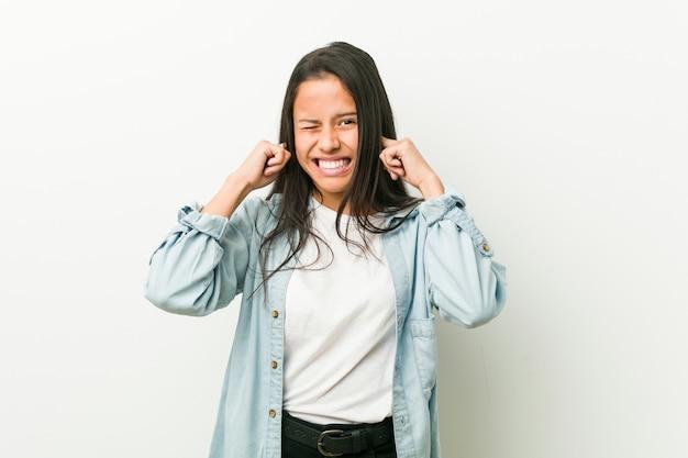 手で耳を覆う若いヒスパニック系女性。