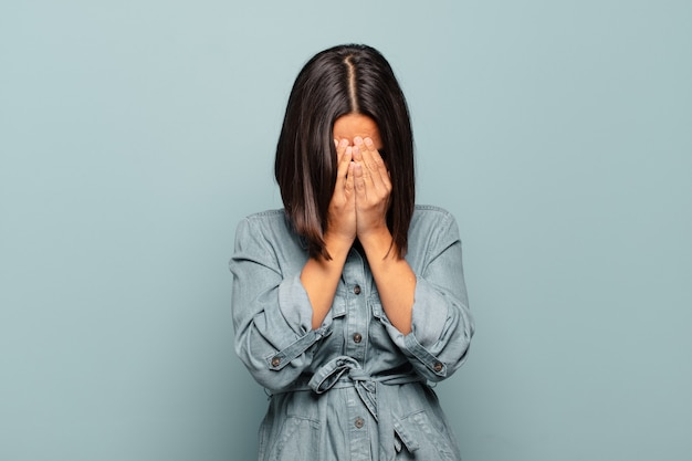 Young hispanic woman covering eyes with hands with a sad, frustrated look of despair, crying, side view