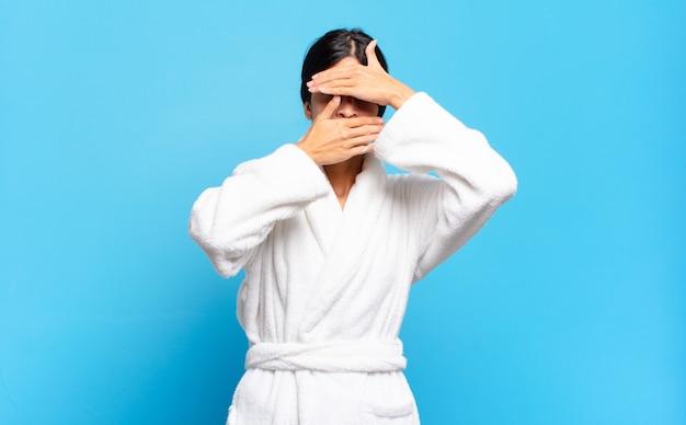 Молодая латиноамериканка закрыла лицо обеими руками, говоря «нет»! отказ от фотографий или запрет на фотографии. халат концепция