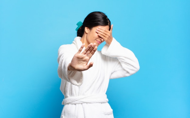 Young hispanic woman covering face with hand and putting other hand up front to stop camera, refusing photos or pictures. bathrobe concept
