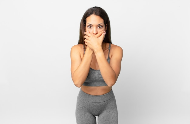 ショックを受けた手で口を覆っている若いヒスパニック系女性。フィットネスコンセプト