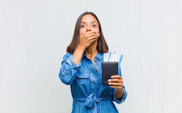 Молодая латиноамериканка закрывает рот руками с шокированным, удивленным выражением лица, хранит секрет или говорит: ой
