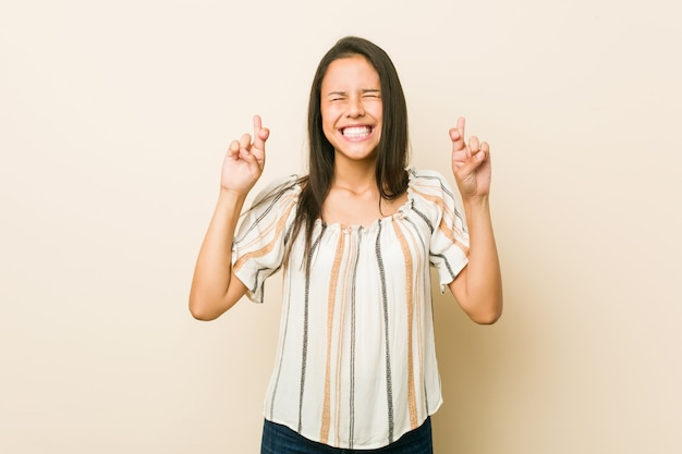Young hispanic woman crossing fingers for having luck