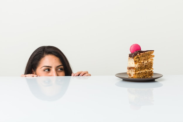 Young hispanic woman dreaming with a cake