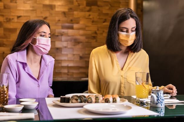 ヒスパニック系の若い女性が日本食レストランで寿司を食べる健康的な食事をしている陽気な友人のためのフェイスマスクを身に着けているライフスタイルの新しい通常の夕食黄色とラベンダー2021年の色