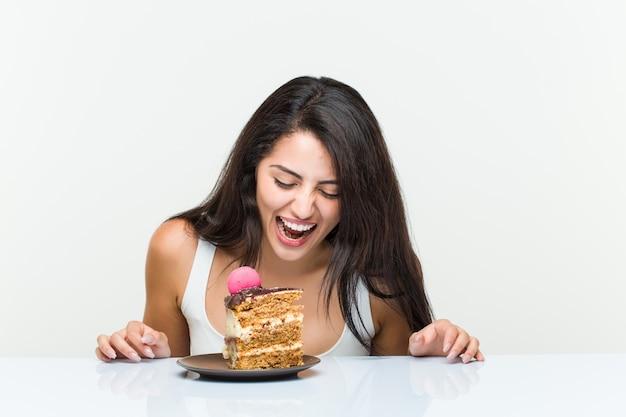 Молодая латиноамериканская женщина ест морковный торт