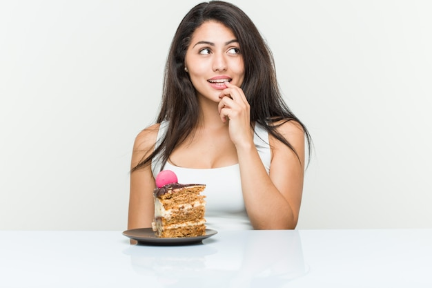 Young hispanic woman eating a cake relaxed thinking about something looking at a .