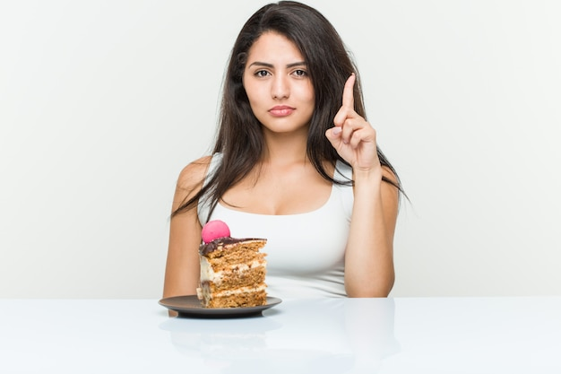 Young hispanic woman eating a cake showing number one with finger.