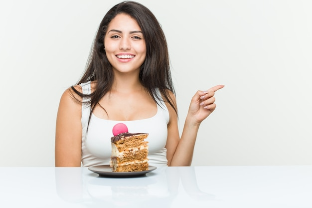 Young hispanic woman eating a cake smiling cheerfully pointing with forefinger away.