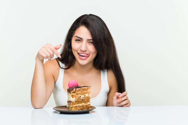 Young hispanic woman eating a carrot cake