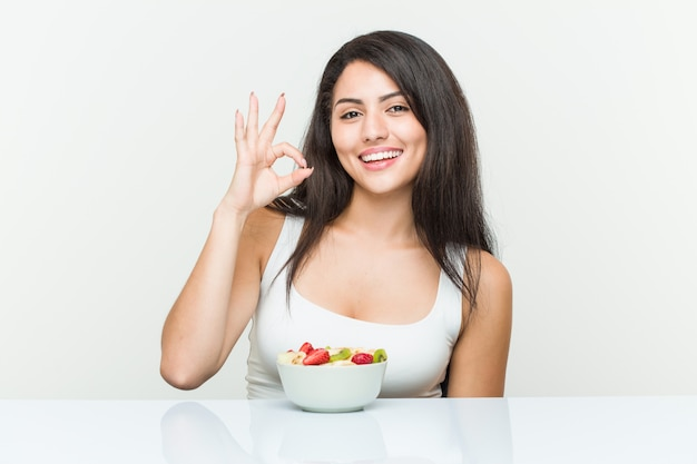 Young hispanic woman eating a fruit bowl cheerful and confident showing ok gesture.