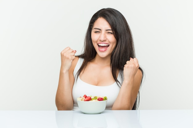 Young hispanic woman eating a fruit bowl cheering carefree and excited
