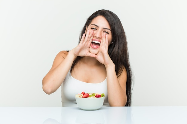 Young hispanic woman eating a fruit bowl shouting excited to front.