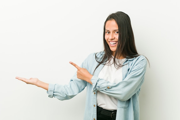 Young hispanic woman excited holding a copy space on palm.