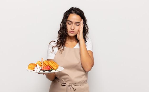 Молодая латиноамериканка чувствует скуку, разочарование и сонливость после утомительной, скучной и утомительной работы, держась за лицо рукой
